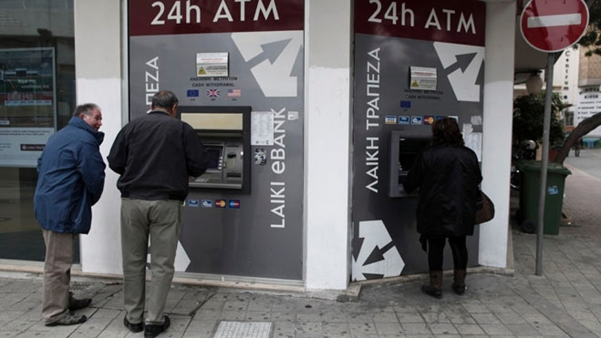March 19, 2013: Cypriots use the ATM machines outside of a closed Laiki Bank branch in capital Nicosia, Cyprus. Cypriot finance officials are revising a planned financial bailout to relieve small account holders from having to pay a charge on their savings in order to secure an international rescue of the country's troubled banks.
