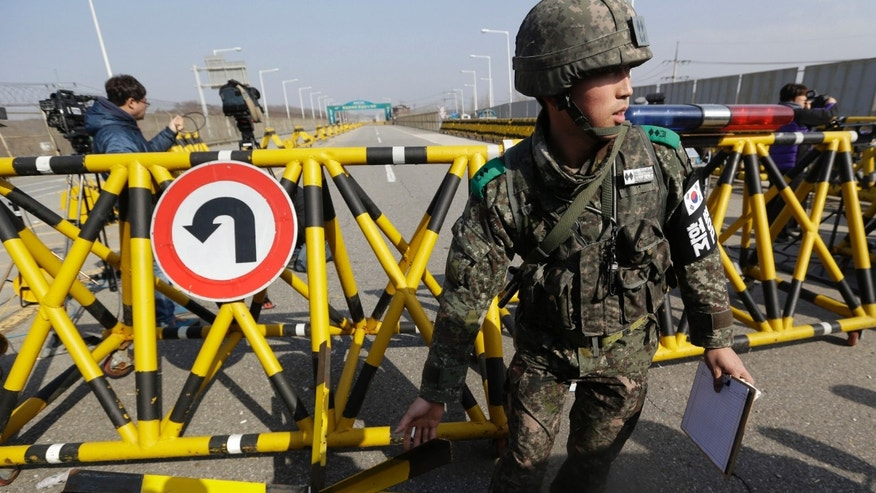 A South Korean army soldier moves a part of barricade for the media to enter at Unification Bridge near the border village of Panmunjom, that has separated the two Koreas since the Korean War, in Paju, north of Seoul, South Korea, Tuesday, April 9, 2013. North Korean workers didn't show up for work at a jointly run factory complex with South Korea on Tuesday, a day after Pyongyang suspended operations at the last remaining major economic link between rivals locked in an increasingly hostile relationship. (AP Photo/Lee Jin-man)