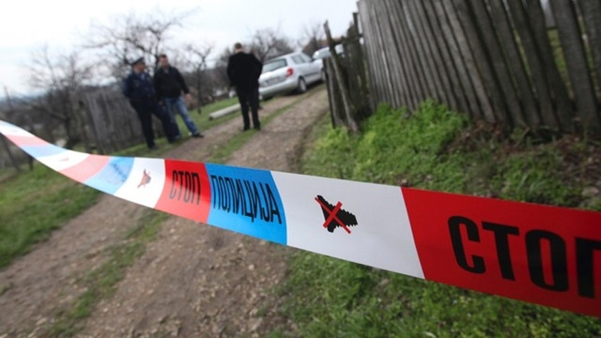April 9, 2013: Serbian police officers guard house in village of Velika Ivanca, Serbia.