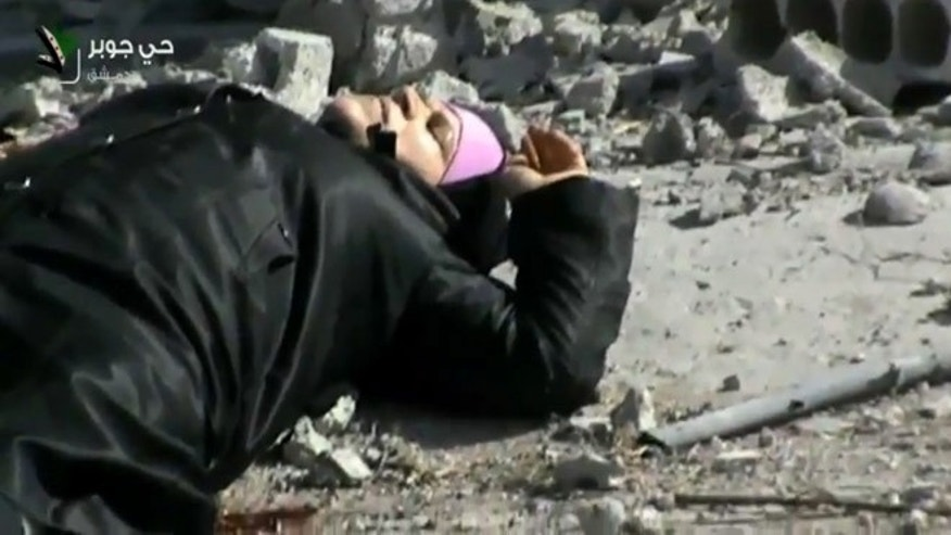 April 10, 2013: This image taken from video obtained from Shaam News Network, which has been authenticated based on its contents and other AP reporting, shows an injured Syrian woman lying in a street before her rescue by rebels from a firefight in the Jobar neighborhood in Damascus, Syria.