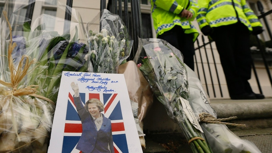 "A card is left on a floral tribute outside former British Prime Minister Baroness Thatcher's home in London, Tuesday, April 9, 2013. Margaret Thatcher, the combative ""Iron Lady"" who infuriated European allies, found a fellow believer in former US President Ronald Reagan and transformed her country by a ruthless dedication to free markets in 11 bruising years as prime minister, died Monday, April 8, 2013. She was 87 years old. (AP Photo/Kirsty Wigglesworth)"