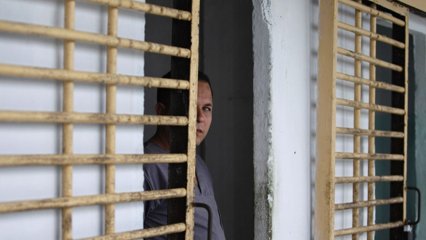 A prisoner looks at members of the press from his cell after the gate was opened by military guards at the Combinado del Este prison during a media tour of the prison in Havana, Cuba, Tuesday, April 9, 2013.  Cuban authorities led foreign journalists through the maximum security prison, the largest in the Caribbean country that houses 3,000 prisoners. Cuba says they have 200 prisons across the country, including five that are maximum security. (AP Photo/Franklin Reyes)