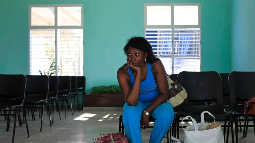 A woman, who did not want to give her name, waits to visit her husband who she said is serving the second year of his 13 year sentence at the Combinado del Este prison, during a media tour in Havana, Cuba, Tuesday, April 9, 2013.  Cuban authorities led foreign journalists through the maximum security prison, the largest in the Caribbean country that houses 3,000 prisoners. Cuba says they have 200 prisons across the country, including five that are maximum security. (AP Photo/Franklin Reyes)