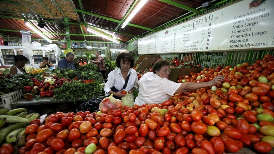 In this April 6, 2013 photo, customers choose tomatoes at a food market in Caracas, Venezuela. Venezuelans complain that what goes into their Sunday dinner plate comes from abroad: Steak, from Brazil; plantains, the Dominican Republic; rice, South Africa; Parmesan cheese, Uruguay; oats, Chile. Even coffee, in a country famed for it, often is Colombian. (AP Photo/Fernando Llano)
