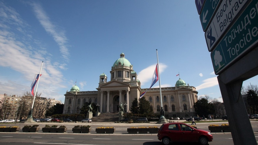 The Serbian flag flies at half-staff on the Serbian Parliament building, Wednesday, April 10, 2013, in Belgrade, Serbia, in honor of six men, six women and a child dead in the village of Velika Ivanca. A 60-year old veteran on Tuesday gunned down 13 people in Serbia, including his mother, his son and a two-year-old cousin before shooting himself and his wife. (AP Photo/Darko Vojinovic)