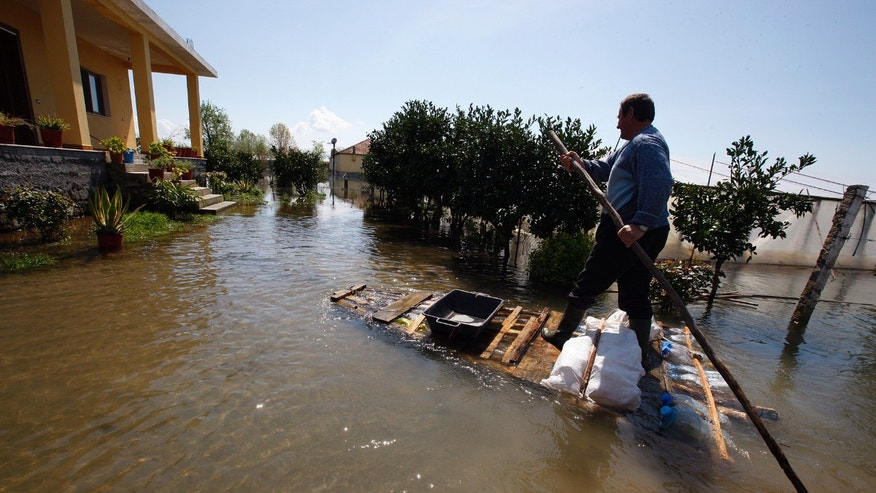 Hil Gjocaj uses a hand-made raft to drive through his yard to his house following a month-long flooding in the village of Obot, near the city of Shkoder, 120 kilometers (75 miles) northwest of capital Tirana, Thursday, April 11, 2013.  Following near continuous rainfall in the region for about a month, some hundreds of families have abandoned their swamped properties and farmers say floods have destroyed their small businesses as lack of food stuffs is taking their livestock to the brink of death, and many complain about of a lack of help from the authorities. (AP Photo/Hektor Pustina)