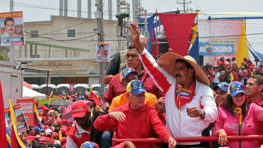 In this photo released by Miraflores Press Office, Venezuela's acting President Nicolas Maduro waves to the crowd as he campaigns in Cabimas, Zulia state, Venezuela, Thursday, April 11, 2013. Maduro, late President Hugo Chavez's hand-picked successor, is running for president against opposition candidate Henrique Capriles on April 14. (AP Photo/Miraflores Press Office)