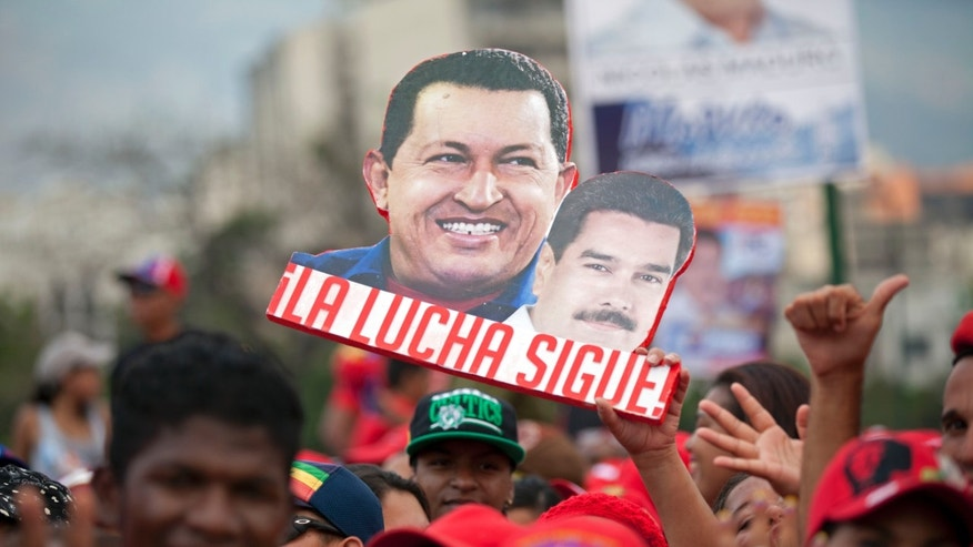 """A supporter holds up a sign that reads in Spanish """"The fight continues"""" and shows late President Hugo Chavez, left, and current presidential candidate Nicolas Maduro, before the closing campaign rally for Maduro in Caracas, Venezuela, Thursday, April 11, 2013. Maduro, Chavez's hand-picked successor, is running for president against opposition candidate Henrique Capriles on April 14. (AP Photo/Ramon Espinosa)"""