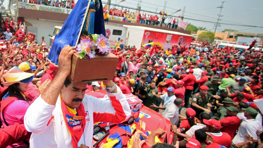 In this photo released by Miraflores Press Office, Venezuela's acting President Nicolas Maduro holds up an image of Saint Benedict as he campaigns in Cabimas, Zulia state, Venezuela, Thursday, April 11, 2013.  Maduro, late President Hugo Chavez's hand-picked successor, will run for president against opposition candidate Henrique Capriles on April 14. (AP Photo/Miraflores Press Office)