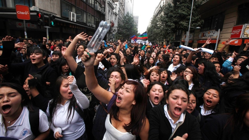 Chilean students march through the streets demanding free education, in Santiago, Chile, Thursday, April. 11, 2013.  The marches began during the 2006-2010 Michelle Bachelet administration and have troubled current President Sebastian Pinera even more. Pinera's government is focusing a chunk of the 2013 budget on financing school loans at lower rates. But students say the system still fails them, with poor public schools, expensive private universities, unprepared teachers and unaffordable loans. (AP Photo/Luis Hidalgo)