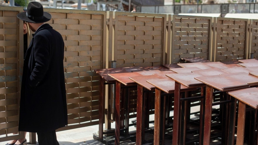 An ultra-Orthodox Jewish man speaks to a woman across a fence separating men and women at the Western Wall, the holiest site where Jews can pray in Jerusalem's old city, Wednesday, April 10, 2013. The rabbi of Judaism's holiest prayer site has backed a proposal to establish a prayer section for mixed-gender worship, a groundbreaking motion that could end a decades-old fight against Orthodox monopoly of the area. (AP Photo/Sebastian Scheiner)