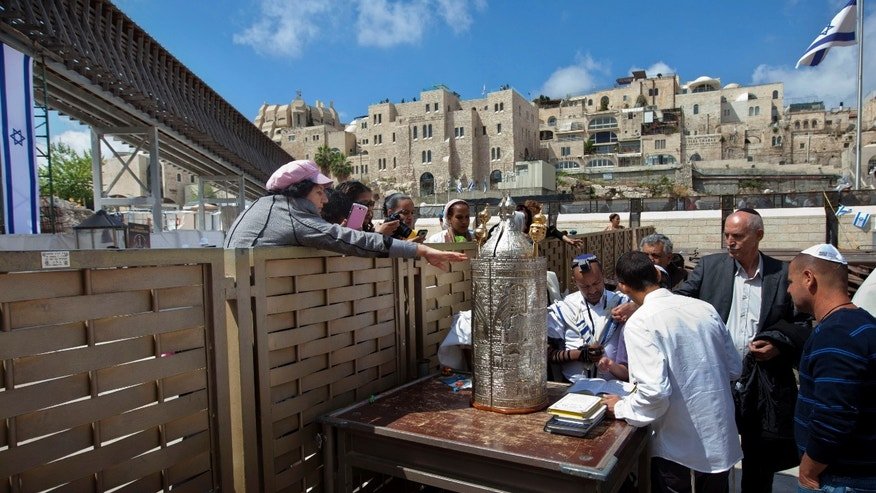 A woman reaches to touch a Torah scroll across a fence at the Western Wall, the holiest site where Jews can pray in Jerusalem's old city, Wednesday, April 10, 2013. The rabbi of Judaism's holiest prayer site has backed a proposal to establish a prayer section for mixed-gender worship, a groundbreaking motion that could end a decades-old fight against Orthodox monopoly of the area. (AP Photo/Sebastian Scheiner)