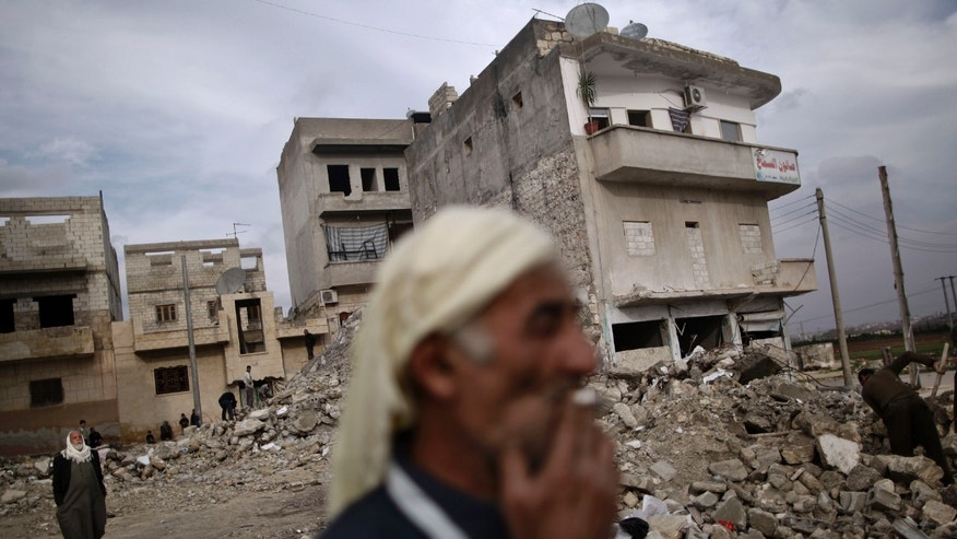 FILE - In this Wednesday, Dec. 12, 2012 file photo, an elderly Syrian man smokes a cigarette as he stands next to a residential building destroyed in a government airstrike, in Maaret Misreen, near Idlib, Syria. A U.S.-based rights group on Thursday accused Syria of war crimes by indiscriminate and sometimes deliberate airstrikes against civilians, killing at least 4,300 people since last summer. (AP Photo/Muhammed Muheisen, File)
