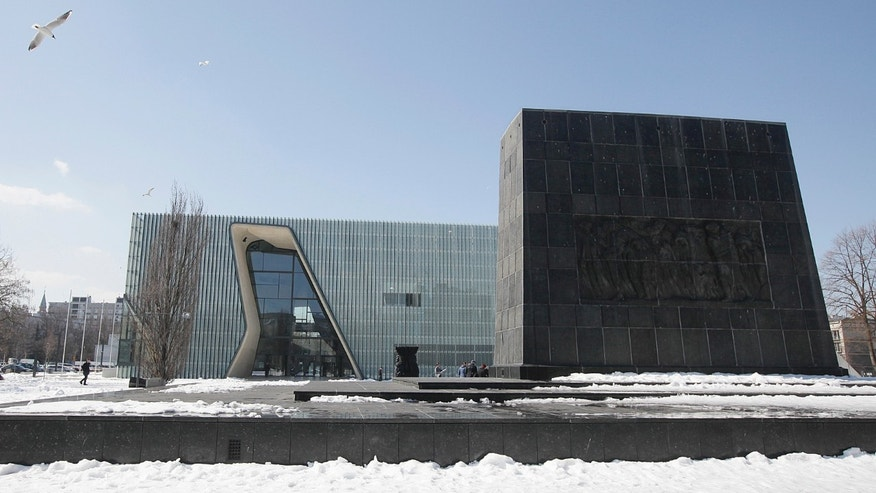 ADVANCE FOR USE MONDAY, APRIL 15, 2013 AND THEREAFTER - This Monday, April 8, 2013 photo shows the Museum of the History of Polish Jews, an ambitious new institution that is opening amid celebrations next week marking the 70th anniversary of the Warsaw Ghetto Uprising. At right is a monument honoring the fighters of the uprising. The revolt gave the world an enduring symbol of defiance against impossible odds, but in a Poland still adjusting to its post-Cold War freedoms, the memory of the Holocaust still engenders controversy in some quarters. The museum that is opening in the ruins of the Jews' prison of misery and death does not shy away from Poland's own history of anti-Semitism a sign, many say, that the country is maturing and riding a wave of confidence-building economic growth. (AP Photo/Czarek Sokolowski)
