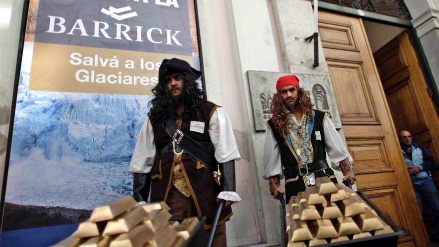 "FILE - In this April 19, 2011 file photo, Greenpeace activists dressed in pirate costumes carrying fake gold protest outside the San Juan state government offices in front of a sign that reads in Spanish ""Stop Barrick, save the glaciers"" in Buenos Aires, Argentina.  Canada's mining company Barrick Gold is developing a large mine in San Juan and has appealed for court injunctions in order to avoid being audited, as it should according to Argentina's Glaciers Law, to corroborate if the mine activity is affecting the glaciers in southern Argentina. There are increased risks for the mining industry in Latin America, where people are taking a closer look at how mining is regulated and taxed, and are determined to capture more of the profits while protecting their natural resources. (AP Photo/Natacha Pisarenko, File)"