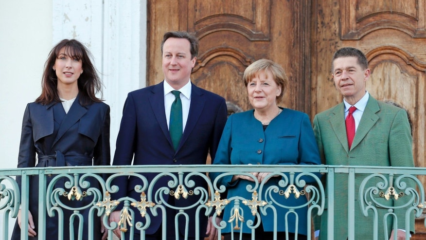 German Chancellor Angela Merkel and her husband Joachim Sauer , right, welcome Britain's Prime Minister David Cameron and his wife Samantha, left, at the government's guest house Schloss Meseberg, 70 km (44 miles) north of Berlin April 12, 2013. (AP Photo/Pool/Fabrizio Bensch)