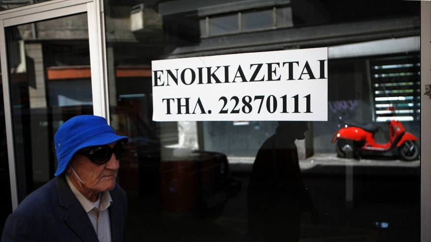 "An elderly man passes  an empty closed shop with a sign reading in Greek "" To rent"" in central Nicosia, Cyprus, Tuesday, April 9, 2013. Last month, Cyprus agreed that bondholders, investors and savers with more than 100,000 euros in the country's two largest — and most troubled — banks will take significant losses in exchange for a 10 billion euro ($13 billion) rescue package. (AP Photo/Petros Karadjias)"