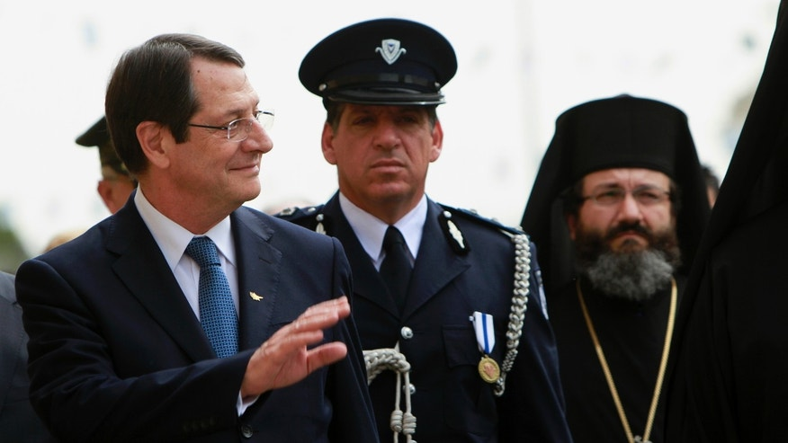 April 1, 2013: Cyprus' President Nicos Anastasiades waves to the people as he reviews the guard of honor during a wreath-laying ceremony at a memorial during the countrys guerrilla campaign against Britains colonial rule between 1955-1959 in Central Prisons for fighters killed in capital Nicosia.