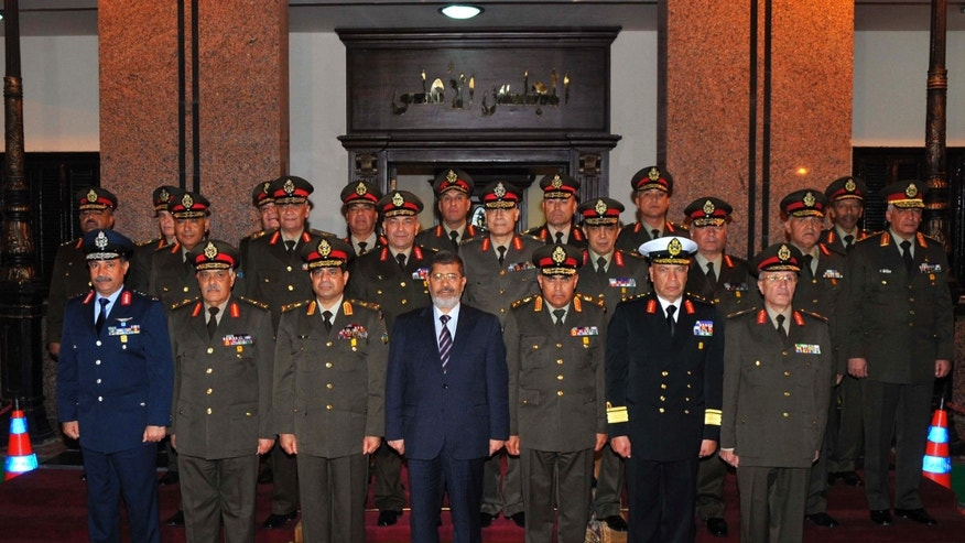 April 11, 2013: In this image released by the Egyptian Presidency, Egyptian President Mohammed Morsi, center, poses with military officers after a meeting with the Supreme Council of the Armed Forces in Cairo, Egypt.