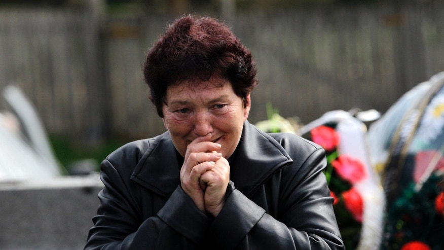 A woman grieves prior to a mass funeral of the victims of a shooting in the village of Velika Ivanca, some 50 kilometers (30 miles) southeast of Belgrade, Serbia, Friday, April 12, 2013. The village  is preparing for the funerals of thirteen victims of a shooting that happened on Tuesday, April 9, 2013. Ljubisa Bogdanovic, a local and a Yugoslav wars veteran, went from house to house on April 9 in the village at dawn, cold-bloodedly gunning down his mother, his son, a 2-year-old cousin and ten other neighbors. (AP Photo/ Darko Vojinovic)