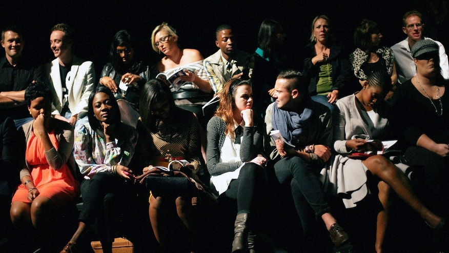 In this photograph taken Thursday April 11, 2013, South Africans wait for the start of a fashion show in Johannesburg.This month, South Africa opened a conversation _ not the first _ over the extent to which the shadow of apartheid drives today's social ills as society fights to overturn entrenched imbalances in services and opportunities. The fresh discussion began with reported comments by Trevor Manuel, national planning minister, that South African officials should assume full responsibility and resist the temptation to continually blame apartheid for missteps.(AP Photo/Jerome Delay)