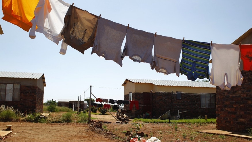FILE - In this image taken Feb. 3, 2012, laundry dries outside a  home  in the  Limpopo  province town of Lebowakgomo, South Africa. This month, South Africa opened a conversation _ not the first _ over the extent to which the shadow of apartheid drives today's social ills as society fights to overturn entrenched imbalances in services and opportunities. The fresh discussion began with reported comments by Trevor Manuel, national planning minister, that South African officials should assume full responsibility and resist the temptation to continually blame apartheid for missteps.(AP Photo/Jerome Delay, file)