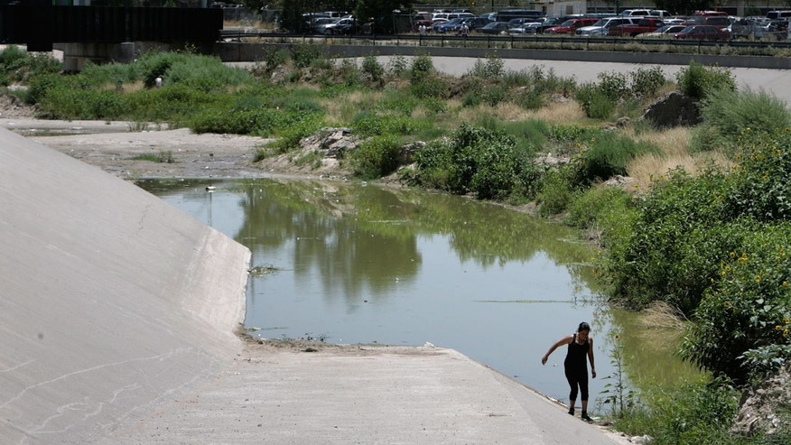 EL PASO, TX - JUNE 26:  A woman moves carefully along the U.S. side of the Rio Grande while attempting to cross the border illegally June 26, 2007 in El Paso, Texas. (Photo by Chip Somodevilla/Getty Images)