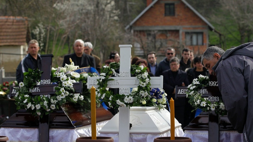 April 12, 2013: A man pays his last respects in front of coffins containing bodies of victims of a shooting prior to a mass funeral in the village of Velika Ivanca, some 30 miles southeast of Belgrade, Serbia.