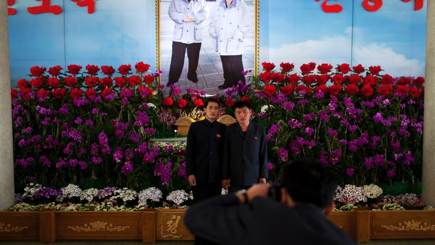"FILE -  In this Friday, April 12, 2013 file photo, two men hold hands as they pose for photos in front of a portrait of the late North Korean leader Kim Jong Il, right, and his son Kim Jong Un at a flower show featuring thousands of Kimilsungia flowers, named after the late leader Kim Il Sung, in Pyongyang, North Korea. Enemy capitals, North Korea said, will be turned ""into a sea of fire."" North Korea's first strikes will be ""a signal flare marking the start of a holy war.""  Pyongyang's nuclear arsenal is ""mounted on launch pads, aimed at the windpipe of our enemies."" And it's not all talk. The profoundly isolated, totalitarian nation has launched two rockets over the past year. But there is also a logic behind North Korea's behavior, a logic steeped in internal politics, one family's fear of losing control and the ways that a weak, poverty-wracked nation can extract concessions from some of the world's most fearsome military powers. (AP Photo/Alexander F. Yuan, File)"