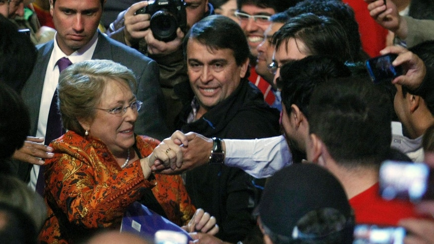 Chile's former President Michelle Bachelet greets supporters before being officially named as candidate for the presidency by the Socialist Party and the Party for Democracy in Santiago, Chile,  Saturday, April 13, 2013.   Bachelet launched her campaign for a new four-year term with an event in the country's capital. She was president from 2006 to 2010, but Chile's constitution bars re-election and she spent the last two years heading the U.N. agency for women and leads in the polls to win this year's election. (AP Photo/Luis Hidalgo)
