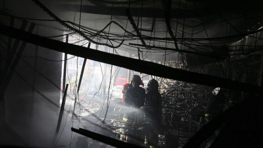 Firefighters extinguish a fire at a hotel in Xiangyang city in central China's Hubei province Sunday, April 14, 2013. A fire at an Internet cafe spread to a hotel in central China on Sunday, killing 11 people and injuring 50 others, state media and firefighters said. (AP Photo) CHINA OUT