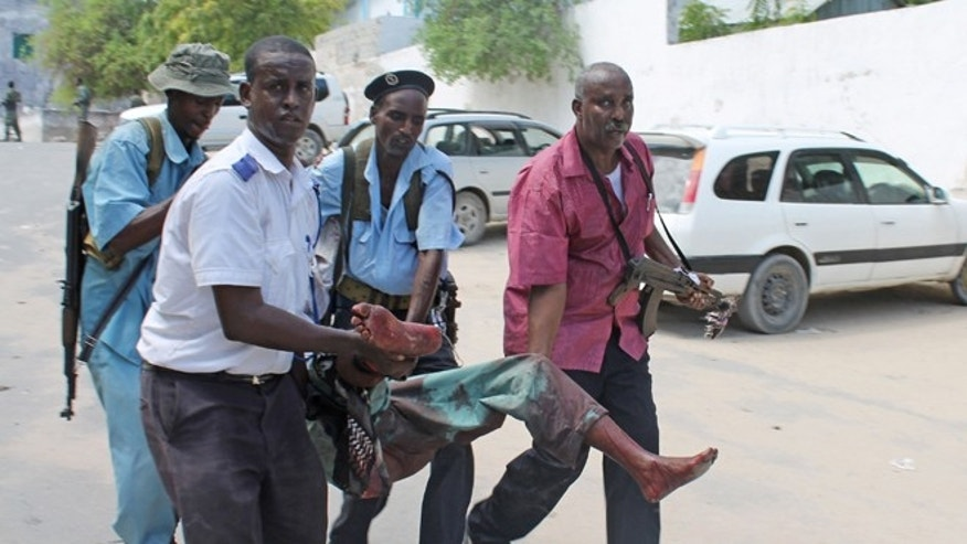 Somali soldiers carry a wounded civilian from the entrance of Mogadishus court complex after being injured during a siege by militants, in Mogadishu, Somalia, Sunday, April 14, 2013. (AP)