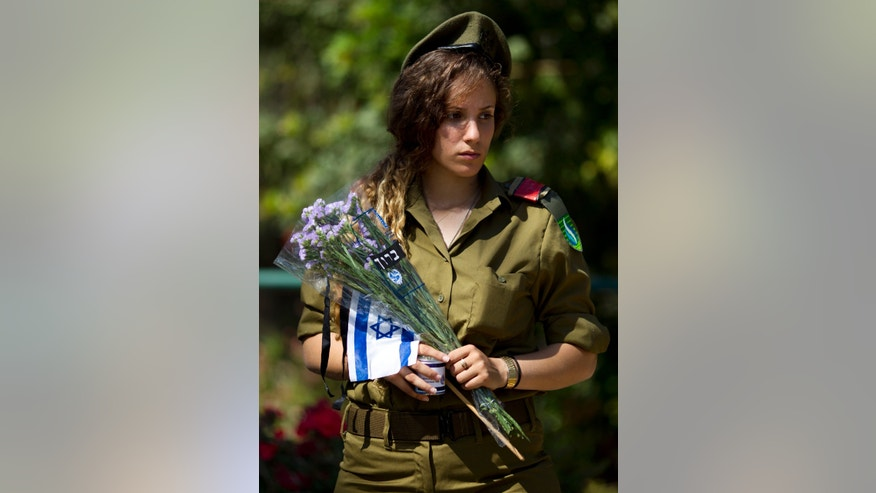 "An Israeli soldiers prepares to place an Israeli flag with a black ribbon and flowers on the graves of fallen soldiers at the Kiryat Shaul Military Cemetery in Tel Aviv, Israel, Sunday, April 14, 2013. Israel will mark the annual Memorial Day in remembrance of soldiers who died in the nation's conflicts, beginning at dusk Sunday until Monday evening. Writing in Hebrew reads, ""blessed."" (AP Photo/Ariel Schalit)"