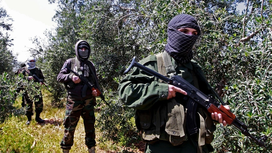 In this Friday, April 12, 2013 photo, members of the Lebanese pro-Syrian Popular Committees stand guard at the Lebanon-Syria border, near the northeastern Lebanese town of al-Qasr, Lebanon. Masked men in camouflage toting Kalashnikov rifles fan out through a dusty olive orchard, part of a group of Hezbollah-backed fighters from Lebanon who are patrolling both sides of a porous border stretch with Syria. The gunmen say their mission to protect Shiites in both countries and counter what they see as a growing threat from Sunni rebels in Syria. (AP Photo/Bilal Hussein)