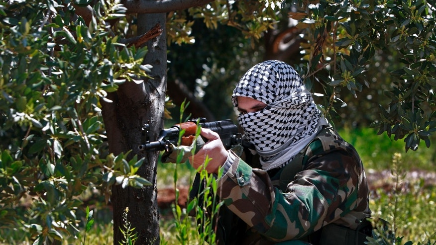 In this Friday, April 12, 2013 photo, a member of the Lebanese pro-Syrian Popular Committees aims his weapon at the Lebanon-Syria border, near the northeastern Lebanese town of al-Qasr, Lebanon. Masked men in camouflage toting Kalashnikov rifles fan out through a dusty olive orchard, part of a group of Hezbollah-backed fighters from Lebanon who are patrolling both sides of a porous border stretch with Syria. The gunmen say their mission to protect Shiites in both countries and counter what they see as a growing threat from Sunni rebels in Syria. (AP Photo/Bilal Hussein)