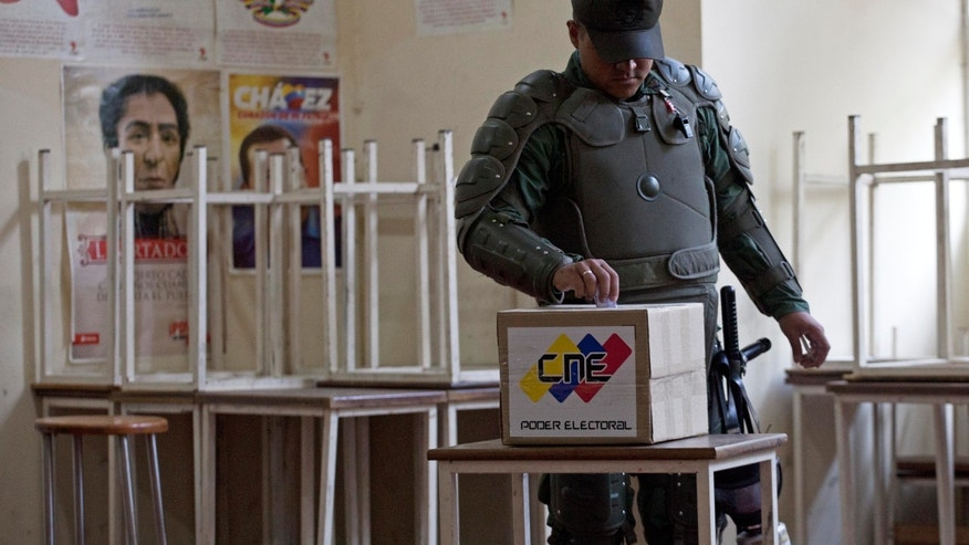 A soldier wearing protective gear casts his ballot during the presidential election at a polling station in Caracas, Venezuela, Sunday, April 14, 2013. Interim President Nicolas Maduro, who served as the late President Hugo Chavez's foreign minister and vice president, is running against opposition candidate Henrique Capriles. (AP Photo/Ramon Espinosa)