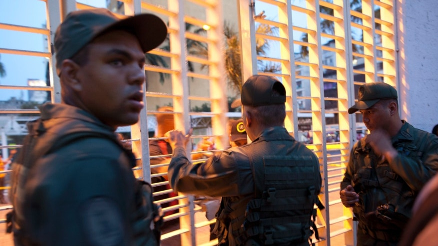 Soldiers close a polling station after a special presidential election in Caracas, Venezuela, Sunday, April 14, 2013. Venezuelan voters were deciding Sunday whether to elect interim President Nicolas Maduro, who served as late President Hugo Chavez's foreign minister and vice president or opposition candidate Henrique Capriles, to replace Chavez who died of cancer on March 5. (AP Photo/Ramon Espinosa)