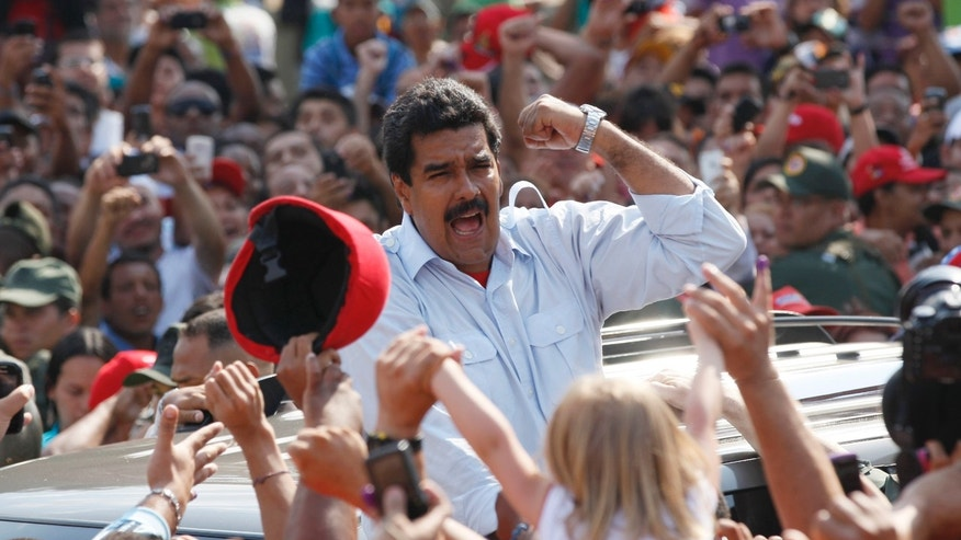 Venezuela's interim President Nicolas Maduro gestures to supporters as he leaves a polling station after voting in the presidential election in Caracas, Venezuela, Sunday, April 14, 2013.  Maduro, who served as late President Hugo Chavez's foreign minister and vice president, is running against opposition candidate Henrique Capriles. (AP Photo/Ariana Cubillos)