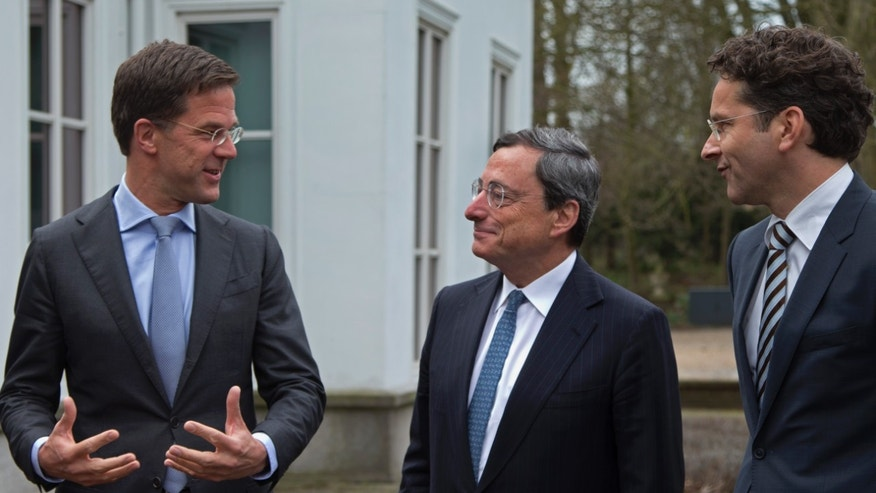 Dutch Prime Minister Mark Rutte, European Central Bank chief Mario Draghi, and Eurogroup President and Dutch Finance minister Jeroen Dijsselbloem, from left to right, pose for photographers prior to a meeting in The Hague, Netherlands, Monday April 15, 2013. Draghi will address Amsterdam students later in the day on the role of monetary policy in addressing the European debt crisis. (AP Photo/Peter Dejong)