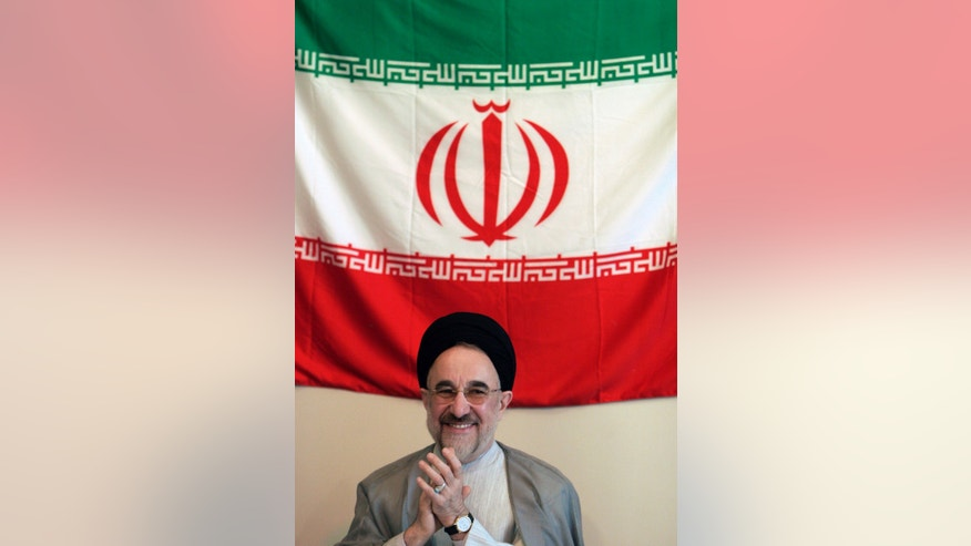 In this undated photo released by office of former Iranian President Mohammad Khatami, Mohammad Khatami, claps under a national Iranian flag, in Italy. Many reformists are expected to sit out the June 14 voting in a silent protest over the crackdowns that have left them leaderless and demoralized. Others unwilling to boycott the election are rallying around a last-ditch call for help to Khatami, who is seen increasingly as their only credible hope at the ballot box. (AP Photo/Office of Mohammad Khatami)