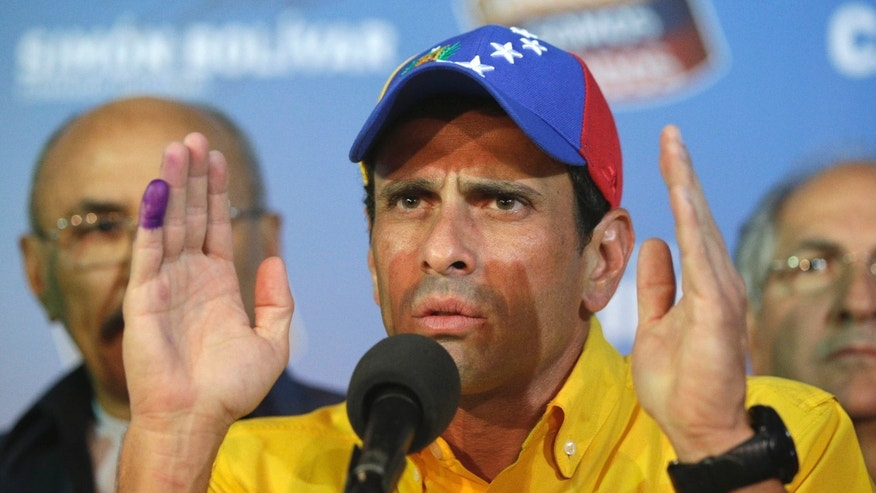 Opposition presidential candidate Henrique Capriles talks to journalist after official results of the presidential elections were announced in Caracas, Venezuela, early Monday April 15, 2013. Capriles is refusing to accept the results of Sunday's presidential election and is demanding a recount.  The official returns announced by the government-dominated electoral council gave the late President Hugo Chavez's chosen successor, Nicolas Maduro, a narrow victory - 50.7 percent to 49.1 percent.(AP Photo/Fernando LLano)
