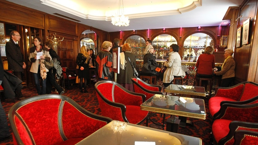 Visitors take a look at furniture displayed for auction in the bar of the Crillon Hotel in Paris, Monday April 15, 2013. Located Place de la Concorde, the Crillon hotel  will put most of its furniture and some of his fine wines under the hammer next week, before a two-year restauration.(AP Photo/Remy de la Mauviniere)