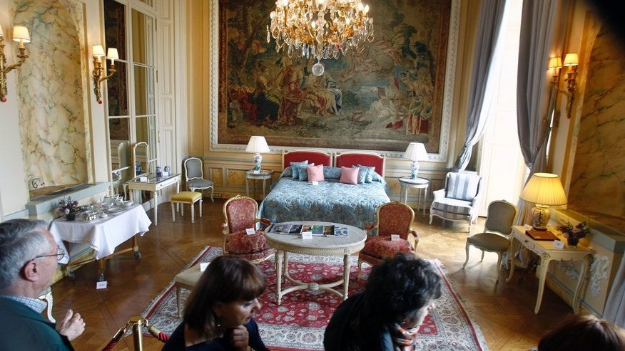 Visitors take a look at furniture displayed for auction at the Crillon Hotel in Paris, Monday April 15, 2013. Located Place de la Concorde, the Crillon hotel  will put most of its furniture and some of his fine wines under the hammer next week, before a two-year restauration.(AP Photo/Remy de la Mauviniere)