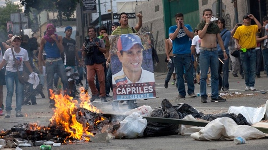 Demonstrators, one holding a poster of opposition presidential candidate Henrique Capriles, confront riot police from behind a burning barricade in the Altamira neighborhood in Caracas, Venezuela, Monday, April 15, 2013.