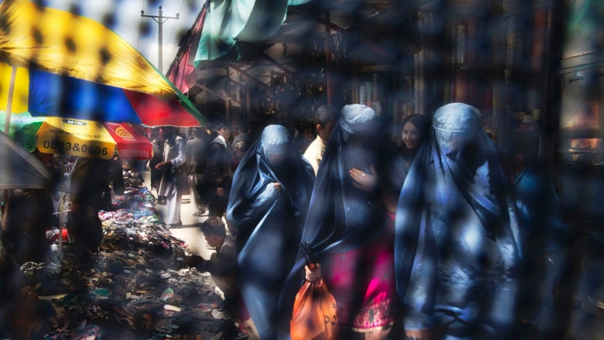 This Thursday, April 11, 2013 photo taken through the eye slit of a burqa, shows Afghan women in Burqa's shopping at a market in Kabul, Afghanistan, Thursday, April 11, 2013. Despite advances in women's rights, Afghanistan remains a deeply conservative country and most women continue to wear the Burqa. But tradesmen say times are changing in Kabul at least, with demand for burqas declining as young women going to school and taking office jobs refuse to wear the cumbersome garments. (AP Photo/Anja Niedringhaus)