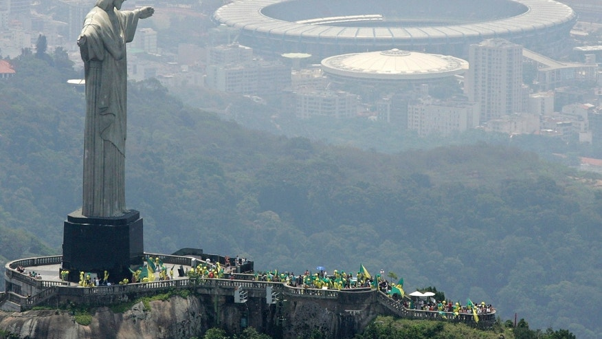 "FILE - In this Oct. 30, 2007 file photo, people wave flags at the top of Corcovado mountain, in front of the statue, Christ the Redeemer, in Rio de Janeiro, after Brazil was officially chosen by FIFA as the host country for the 2014 World Cup. Brazil's foreign minister says ""all necessary measures"" are being taken to ensure security at next year's soccer World Cup and the 2016 Olympics following the deadly explosions at the Boston Marathon. While Brazil has never been a target of international terrorism, Monday's attacks underscore how vulnerable big sporting events can be. Rio will also host two major events later this year, the Confederations Cup soccer tournament and the World Youth Day, a Roman Catholic pilgrimage that's expected to be attended by Pope Francis and as many as 2.5 million visitors. (AP Photo/Andre Penner, File)"