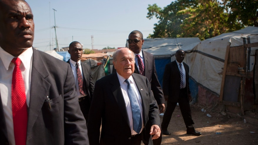 FIFA President Joseph Sepp Blatter, center, walks through a refugee camp set up for people displaced by the 2010 earthquake near the national stadium in Port-au-Prince, Haiti. Tuesday April 16, 2013. During a press conference in Haiti, a top FIFA official said the international football organization will be stepping up security for the 2014 FIFA World Cup in Brazil as a result of the bombings at the Boston Marathon. (AP Photo/Dieu Nalio Chery)
