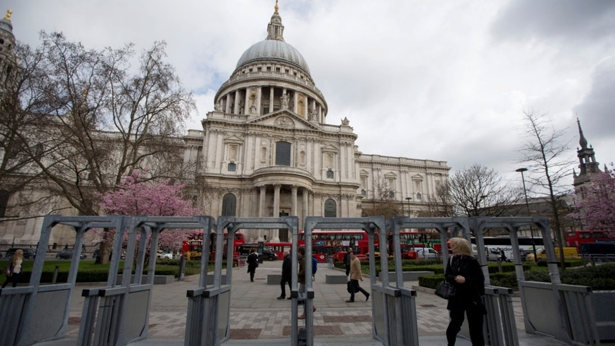 A woman walks through security barriers put up outside St Paul's Cathedral in London, Tuesday, April 16, 2013. British police are reviewing security plans for Sunday's London Marathon, the next major international marathon, because of the bombs that killed three people at the race in Boston.  Police already were preparing a major security operation for Wednesday's ceremonial funeral for former Prime Minister Margaret Thatcher, an event at St. Paul's Cathedral that will be attended by Queen Elizabeth II and many dignitaries. The funeral's security plans are expected to be reviewed in light of the Boston bombings. (AP Photo/Matt Dunham)