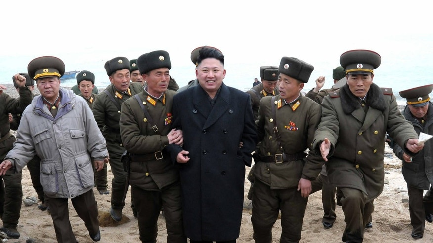 FILE - In this March 7, 2013 photo released by the Korean Central News Agency (KCNA) and distributed March 8, 2013 by the Korea News Service, North Korean leader Kim Jong Un, center, walks with military personnel as he arrives for a military unit on Mu Islet, located in the southernmost part of the southwestern sector of North Korea's border with South Korea. In his 16 months on the job, Kim's government has raised fears with unusually aggressive threats against Seoul and Washington, and it's not clear whether he will be able to pull back, a feat perfected by his late father, considered a master at brinkmanship. The mystery surrounding Kim Jong Un's intentions has some outsiders predicting nightmare scenarios. (AP Photo/KCNA via KNS, File)