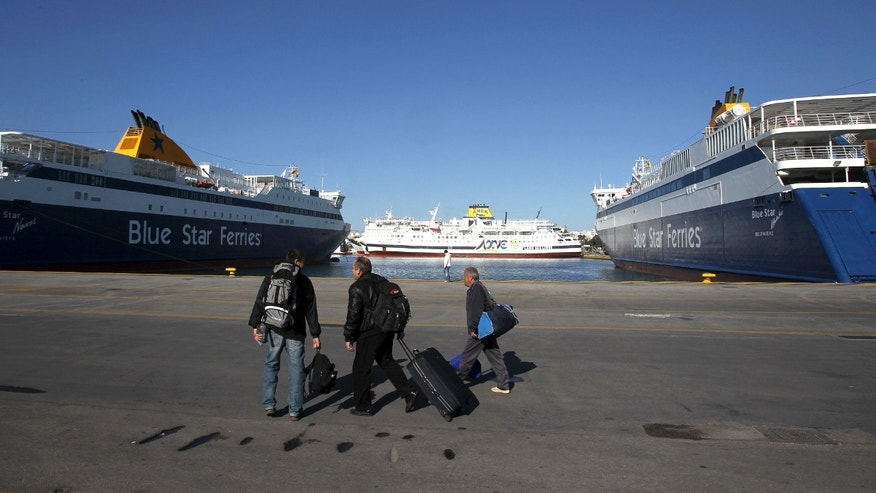 Passengers walk through the port as ferries are moored during a 24-hour nationwide strike by Greek seamen's union in the port of Piraeus, near Athens, Tuesday, April 16, 2013. The union called the strike on Tuesday to protest labor reforms that unions say will undermine their collective bargaining rights. The new draft bill is due to be debated in Parliament on the day of the strike. (AP Photo/Thanassis Stavrakis)
